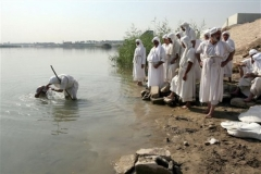 A Mandaean Sabian priest baptizes a believer on the banks of the Tigris river in Baghdad, Iraq, Monday, Nov. 5, 2007. Mandaeanism is a monotheistic religion whose followers regard John the Baptist as their prophet. The Iraq conflict reduced the number of Mandaeans living in the country to approximately five thousand, as most of them fled to neighboring countries under threat of violence. (AP Photo/Hadi Mizban)